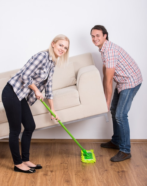 Man raises the sofa while the girl cleans. Premium Photo