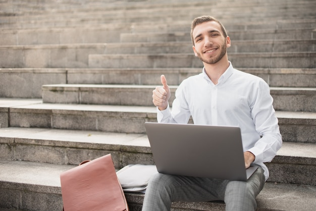 Man raising his big finger up while sitting on stairs Free Photo