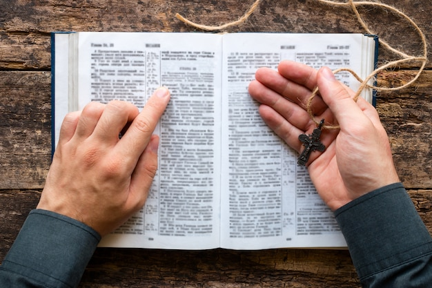 Man reading a bible and holding a cross Premium Photo
