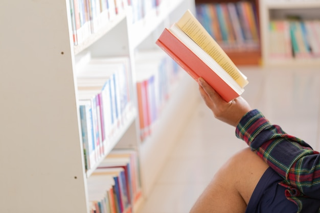 Man reading. book in his hands in library. Free Photo