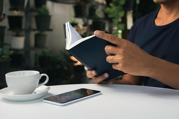 A man reading a book with coffee cup. man sitting in chair at home, reading book and relaxing. Premium Photo