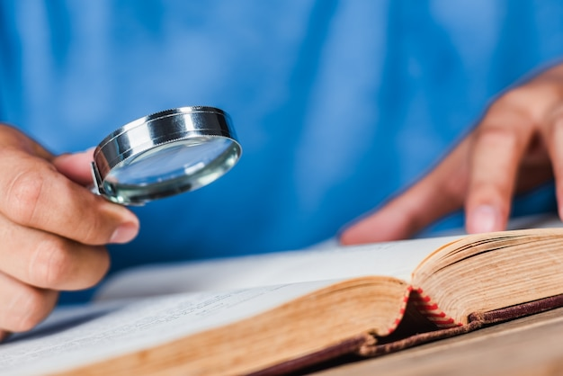 A man reading an old book with magnifying glass Premium Photo