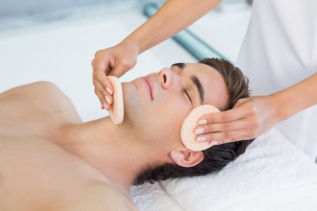 Man receiving facial massage at spa center Premium Photo