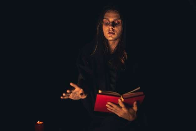 Man reciting a red spell book in the dark Free Photo