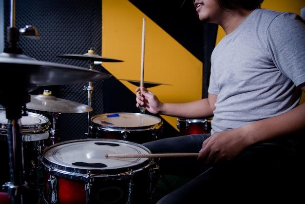 Man recording music on drum set in studio Free Photo