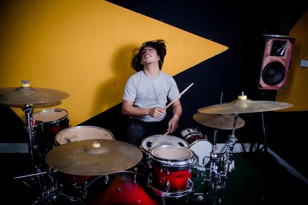 スタジオでドラムセットの音楽を録音する男 無料写真