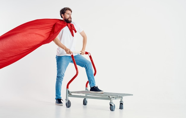 Man in a red coat jeans t-shirt cargo trolley light background copy space Premium Photo