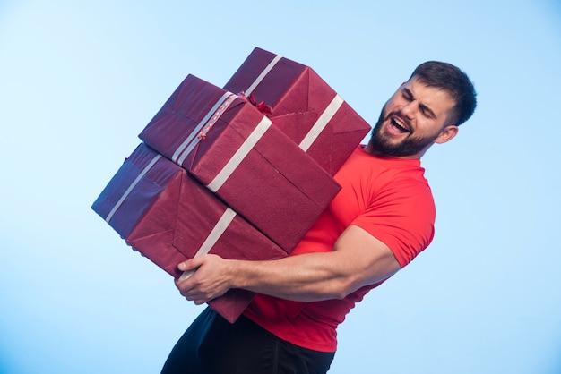 Uomo in camicia rossa che tiene una scorta pesante di scatole regalo. Foto Gratuite
