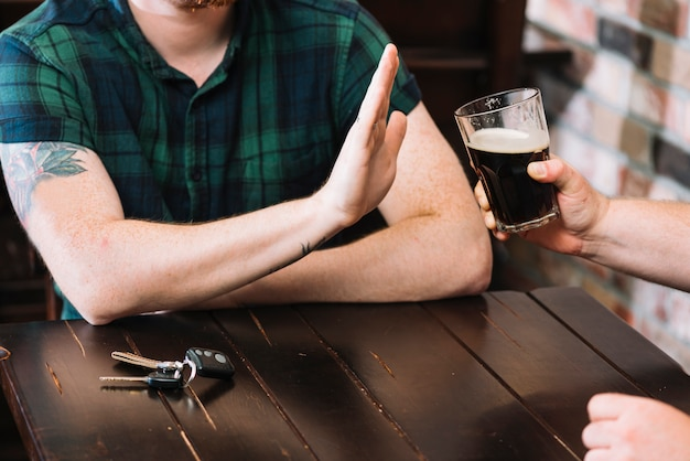 Man refusing glass of rum offered by his friend Free Photo