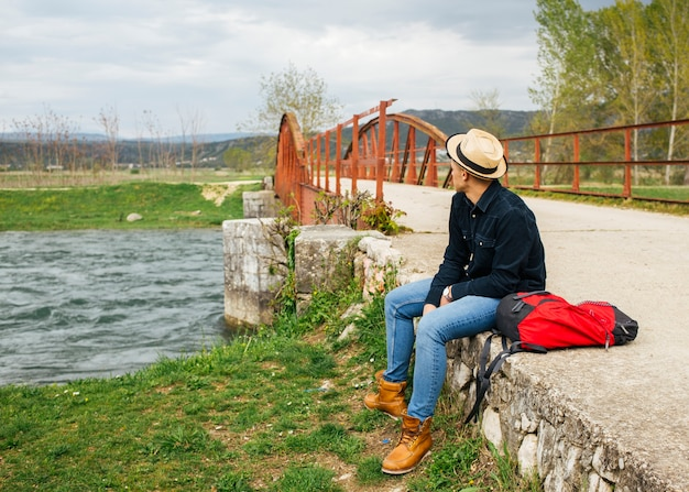 Man relax siting bank of flowing river Free Photo
