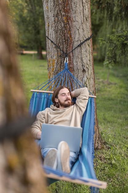 Человек отдыхает в гамаке во время работы на ноутбуке Бесплатные Фотографии