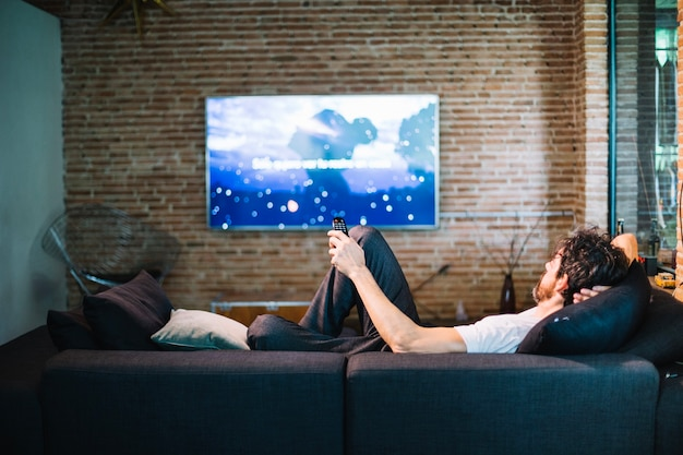 Man relaxing on sofa at home Free Photo