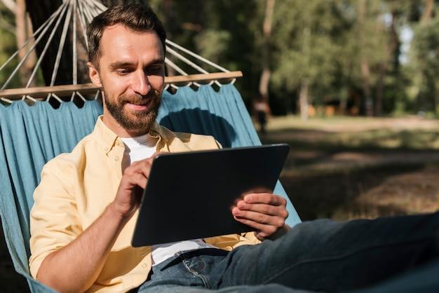 Человек расслабляющий с планшетом в гамаке во время кемпинга Бесплатные Фотографии