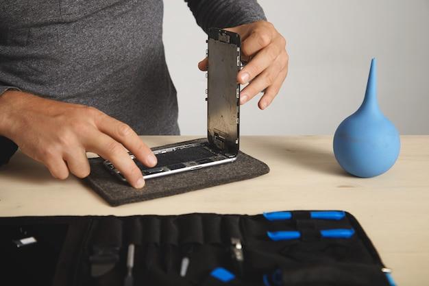 男はスマートフォンの壊れた画面を削除して変更する、電子修理サービス 無料写真