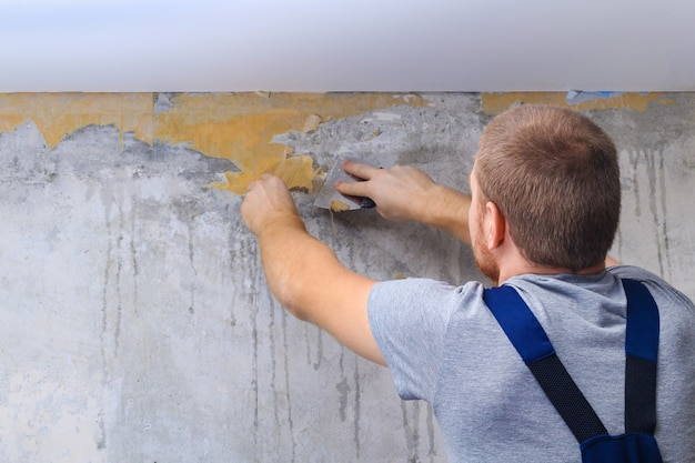 A man removes old wallpaper with a spatula and a spray bottle with water. Premium Photo