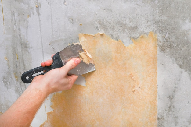 A man removes old wallpaper with a spatula and spray bottle with water. Premium Photo