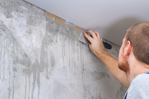 A man removes old wallpaper with a spatula and spray bottle with water Premium Photo