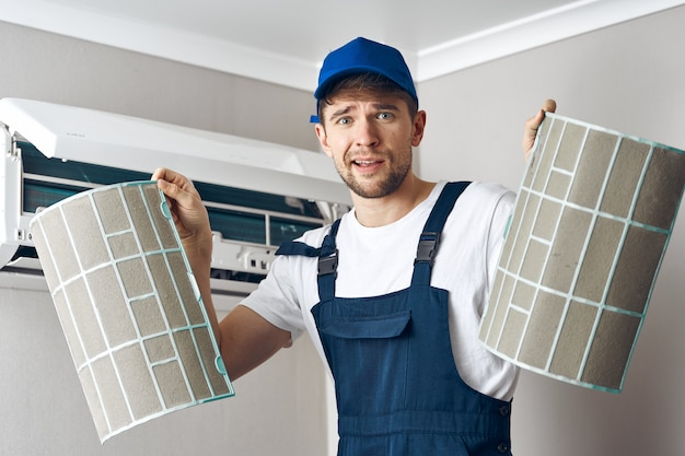 Man repair and cleaning air conditioner, worker at home Premium Photo