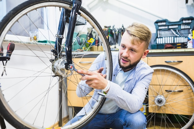Man repairing bicycle tire with wrench Free Photo