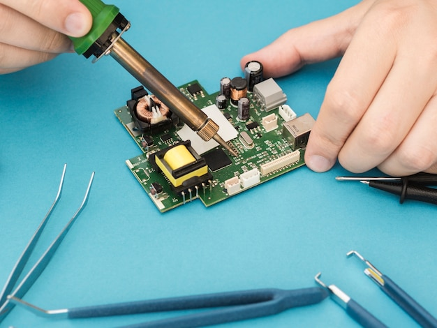 Man repairing a circuit with soldering iron Free Photo