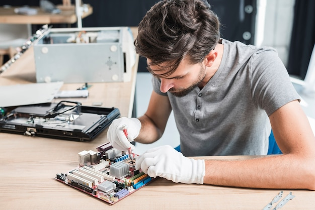 Man repairing electronic circuit of computer Free Photo