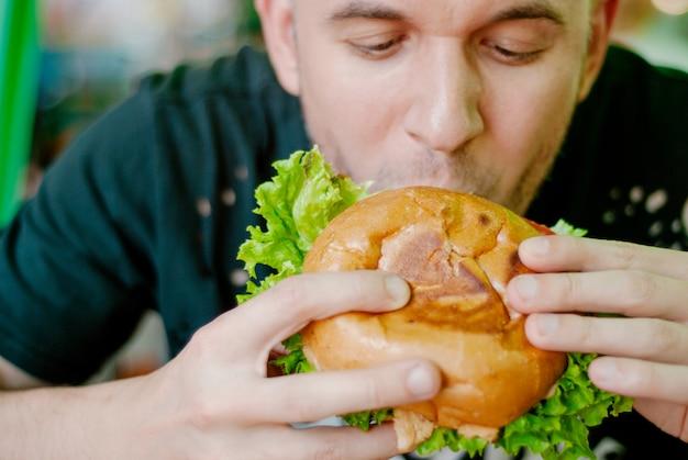 Man in a restaurant eating a hamburger Premium Photo