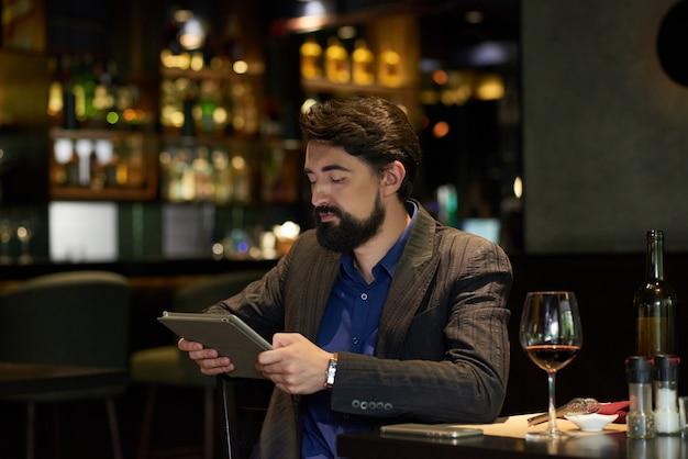 Man in restaurant reading news online Free Photo
