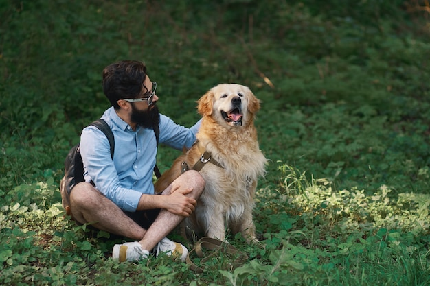 Man resting on the grass sitting crossed legs with his dog Free Photo