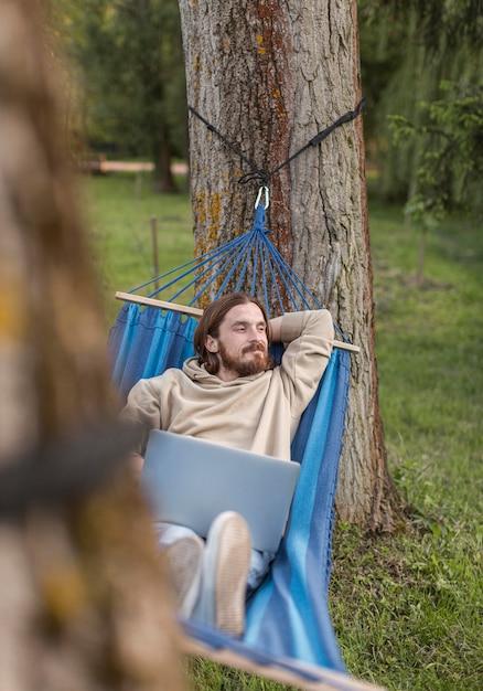 Человек отдыхает в гамаке с ноутбуком Бесплатные Фотографии