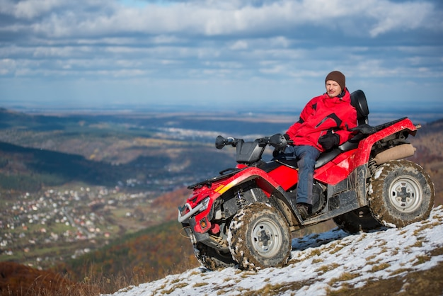Man resting on a red atv bike on a snowy mountain top Premium Photo