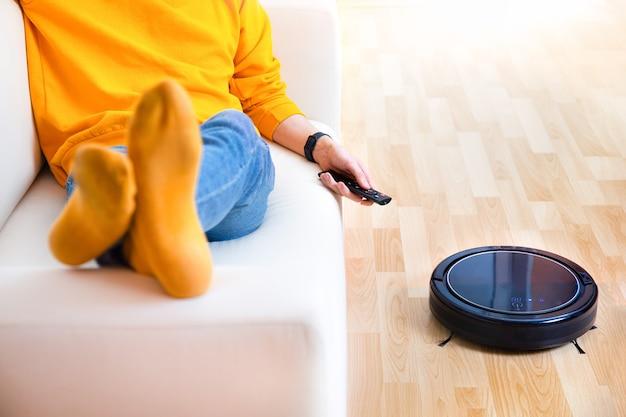 ロボット掃除機が雑用をしている間休んでいる人、家できれいな仕事。 Premium写真