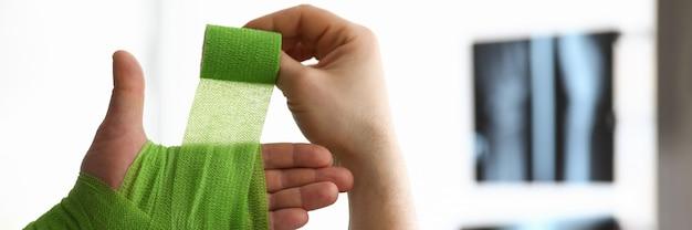 Человек перематывает руку с повязкой на рентгеновском снимке Premium Фотографии