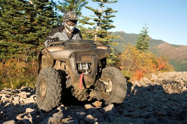 Man riding atv up rocky hill Premium Photo