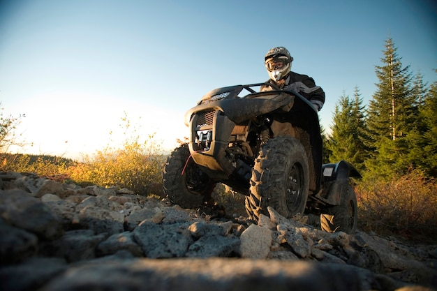 Man riding atv up rocky hill Premium Photo