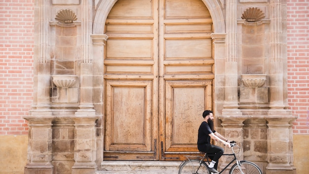A man riding the bicycle in front of an antique closed door Free Photo