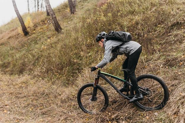 Uomo in sella a una bicicletta sul sentiero di montagna Foto Gratuite