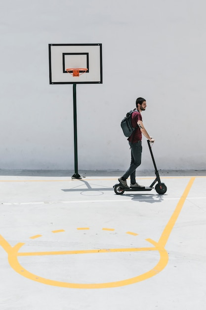 Man riding e-scooter on a basketball court Free Photo
