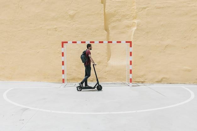 Man riding e-scooter on handball court Free Photo