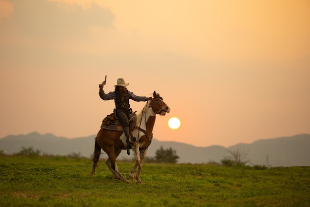 Man riding horse on field during sunset Premium Photo