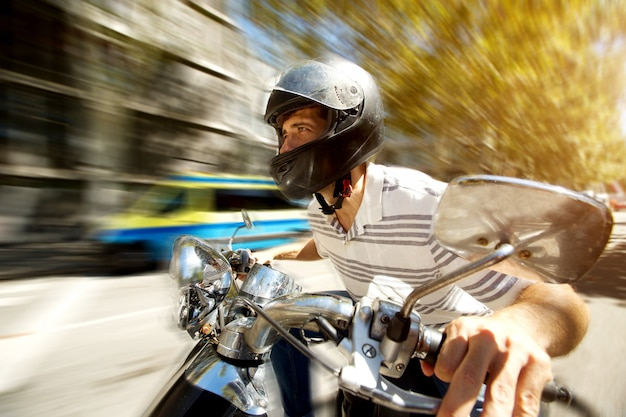 Man riding a scooter at speed on the road with blurred background. Premium Photo