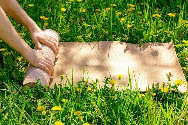Man rolling her mat after a yoga class on a green meadow on a summer sunny day Premium Photo
