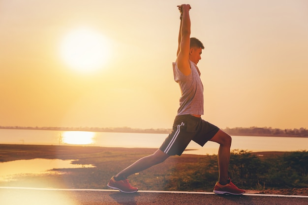 Man runner athletes worming up for outdoor practice with sunset background Premium Photo