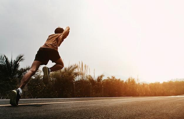 Бегущий человек начинает бегать по дороге Premium Фотографии