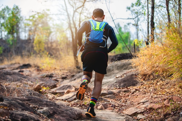 A man runner of trail . and athlete's feet wearing sports shoes for trail running in the forest Premium Photo
