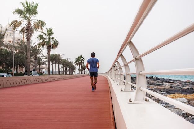 A man runs along a beautiful promenade with a white fence. Premium Photo