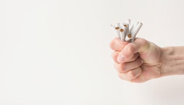 Man's fist creasing cigarettes isolated on white background Free Photo