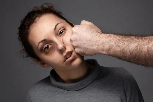 A man's fist hits a woman in the face. Premium Photo