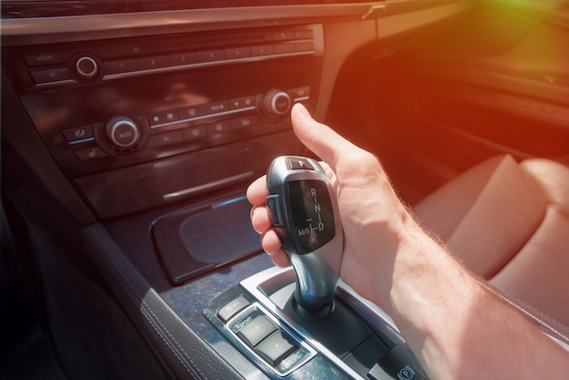Man's hand on an automatic gearbox. Premium Photo