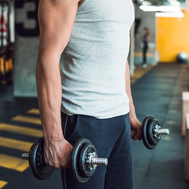 Man's hand doing workout with dumbbells Free Photo