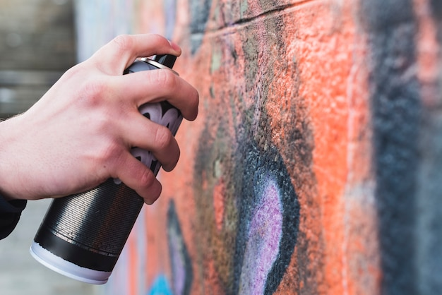 Man's hand drawing graffiti on wall with aerosol can Free Photo